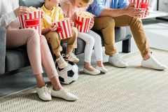 Cropped shot of family eating popcorn while sitting on sofa. With soccer ball royalty free stock image