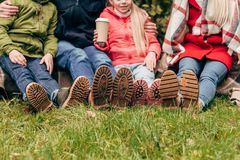 Cropped shot of family wearing autumn shoes and sitting together. In park Royalty Free Stock Images