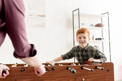 Cropped shot of father and cute smiling son playing table football together. At home stock photo