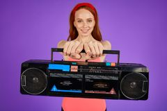 Cropped shot of female aerobics trainer holding portable retro cassette player royalty free stock image