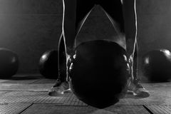 Strong woman working out in gym with heavy ball Stock Images