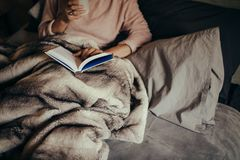 Woman on bed reading book and drinking coffee. Cropped shot of female on bed reading book and drinking coffee. Female reading book on bed at home Royalty Free Stock Photo