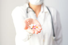 Cropped shot of a female doctor displaying a handful of tablets and pills in her palm Royalty Free Stock Photo
