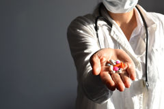 Cropped shot of a female doctor displaying a handful of tablets and pills in her palm Royalty Free Stock Photography