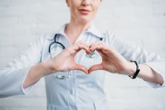 Cropped shot of female doctor showing heart sign. With hands royalty free stock photo