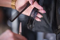 Cropped shot of a female hairdresser cutting clients hair with scissors at beauty salon stock image