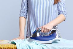 Cropped shot of female hand with electric iron irons husband`s shirt, prepare for birthday party, does housework. Unrecognizable h. Ousewife busy with work Stock Image