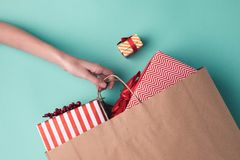 Hand holding paper bag with presents. Cropped shot of female hand holding paper bag with presents Stock Images