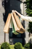 Cropped shot of female hand holding shopping bags. On street stock images