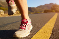 Cropped shot of female jogger running on an empty road Royalty Free Stock Image