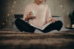 Woman reading book on bed at home. Cropped shot of female sitting on bed reading book and drinking coffee. Woman reading book on bed at home Stock Photos