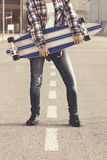 Cropped shot of female with skate. Cropped shot of stylish female holding skateboard standing on road Royalty Free Stock Photography