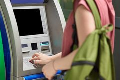 Cropped shot of female teenager carries green bag, wants to withdraw cash, stands near ATM machine, enters pin, makes payment. Sec. Urity, banking and payment Stock Photo
