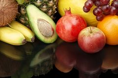 Cropped shot of fruits-grapes,pomegranate,avocado on black with reflection Royalty Free Stock Image