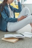 Cropped shot of girl using smartphone while studying. At home stock photos