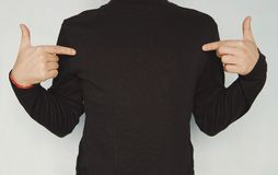Cropped shot of good-looking young unshaven man wearing casual clothes, pointing fingers at copy space on his black blank t-shirt. Clothing, design, style royalty free stock photo