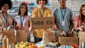 Cropped shot of group of diverse young volunteers packing food and drinks donation, Guy holding card with Thank you