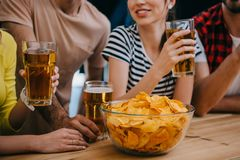 Cropped shot of group of friends with beer and bowl of chips sitting at bar counter during watch of. Soccer match stock photography