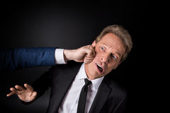 Cropped shot of hand punching middle aged businessman Royalty Free Stock Photos