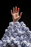 Cropped shot of hand reaching out from heap of crumpled papers. Isolated on black Royalty Free Stock Image