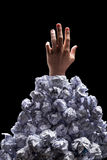 Cropped shot of hand reaching out from heap of crumpled papers. Isolated on black Stock Photos