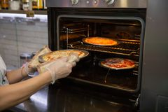 Cropped shot of hands of the cook in kitchen glove taking pizza from oven. Readiness test Royalty Free Stock Photos