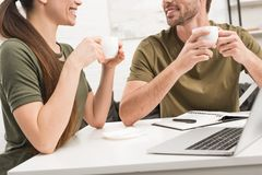 cropped shot of happy couple drinking coffee and working with laptop together stock photography