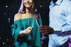 Cropped shot of happy friends with champagne flutes at night club party. Cropped shot of happy male and female multiethnic friends with champagne flutes at night Stock Photo