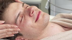 Cropped shot of a happy man enjoying head and face massage at spa center stock video footage