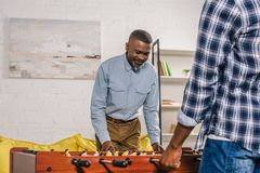 Cropped shot of happy senior father and adult son playing table football. At home stock image