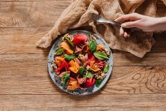 Cropped shot of human hand holding fork and salad with mussels, vegetables and jamon. On wooden table royalty free stock photography