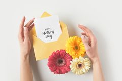 cropped shot of human hands with envelope, gerbera flowers and happy mothers day greeting card on grey Royalty Free Stock Photos