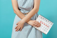 Cropped shot illness woman in blue dress holding periods calendar for checking menstruation days put hand on abdomen. Cropped illness woman in blue dress holding royalty free stock photos