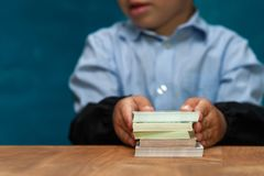 Little stylish boy counting money at workplace. Cropped shot of little boy sitting at workplace, counting money. Cute child imitating bookkeeper or Royalty Free Stock Photos