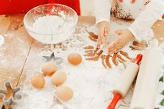 Cropped shot of little child in apron bakes something delicious on kitchen, makes cakes with hands, surrounded with. Rolling pin, eggs and flour, uses special stock photography
