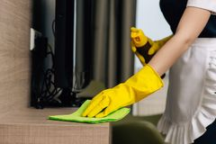Cropped shot of maid in uniform wiping shelf with rag and aerosol. Furniture cleaner stock photos