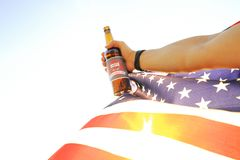 Cropped shot of male hand holding beer bottle & national flag of USA against setting sun. River background. Happy independence day stock photography