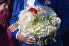 Cropped shot of male holding a generous wedding bouquet featuring white and pale pink roses, freesias and white hydrangeas. Horizontal shot of Caucasian young Royalty Free Stock Photo