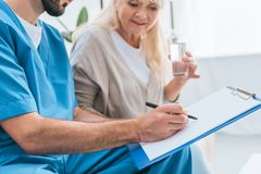 cropped shot of male nurse writing on clipboard and senior woman stock photo