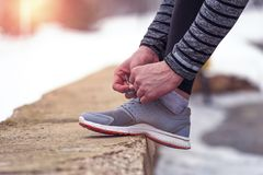 Male runner tying his shoelaces before workout. Cropped shot of male runner tying his shoelaces before running workout outdoors in winter Stock Images