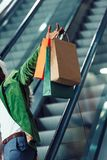 Cropped shot of man holding shopping bags while riding escalator at mall Royalty Free Stock Images