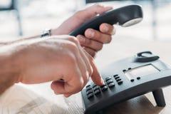 Cropped shot of man making dialing stationary phone to. Make call royalty free stock photos