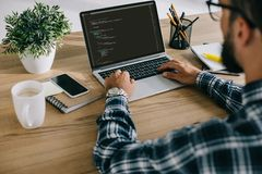 cropped shot of man in plaid shirt using laptop with program code royalty free stock photos