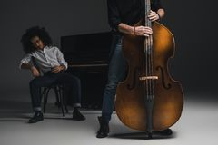 Cropped shot of man playing violoncello while his depressed partner sitting at piano blurred. On background royalty free stock photo