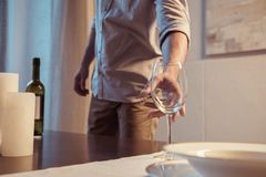 cropped shot of man serving table with wine glass stock photo
