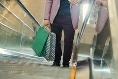 Cropped shot of man with shopping bags on escalator Stock Photo