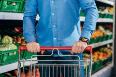 Cropped shot of man with shopping cart. In grocery shop Stock Image