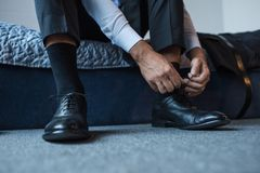 Cropped shot of man sitting on bed and tying laces on black. Leather shoes Royalty Free Stock Photo