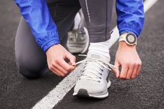 Cropped shot of a man tying his shoelaces on running shoes. Stock Images