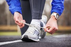Cropped shot of a man tying his shoelaces on running shoes. Royalty Free Stock Image